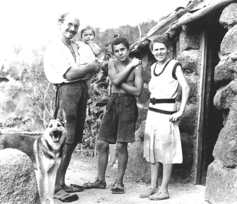 ウィットマー・ファミリー。1933年、自宅前でのショット。向かって左からハインツ、写真では誰かが配慮なくコントラストを上げたせいで空の境目と頭部の境界線が曖昧になって一体化しているように見える。そのハインツに抱かれているのがロルフ。そしてドイツにいた頃は病弱だったものの島暮らしで意外なサバイバルの才能を開花させたというハリー少年、若妻マルグレット。足下のジャーマン・シェパードはランプという名で、家族とともによく働いた。家にいるマルグリットがメモ書きをくわえさせると、ランプがそれを出先のハインツの元まで運ぶという――伝達役もできるとても利口な犬だった。画像出典:The Galapagos Affair: Satan Came to Eden